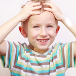 child holding his head smiling 2
