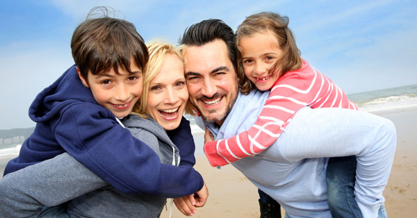 smiling family of four at the beach 3