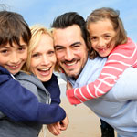 smiling family of four at the beach 4