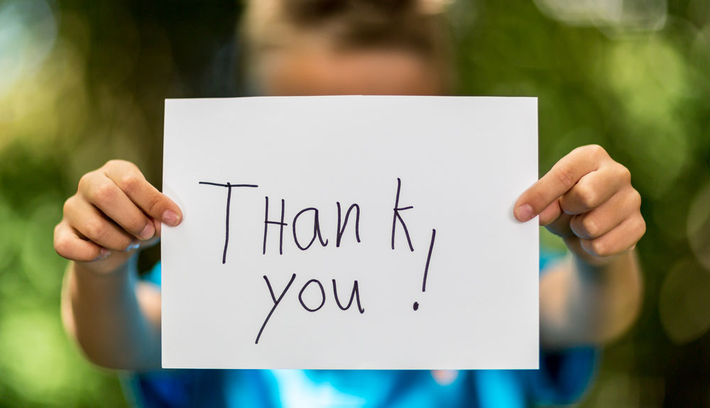 child holding a thank you sign 3