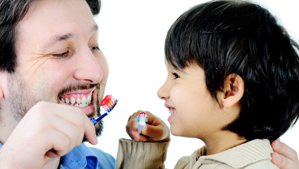 father and son brushing their teeth together 2