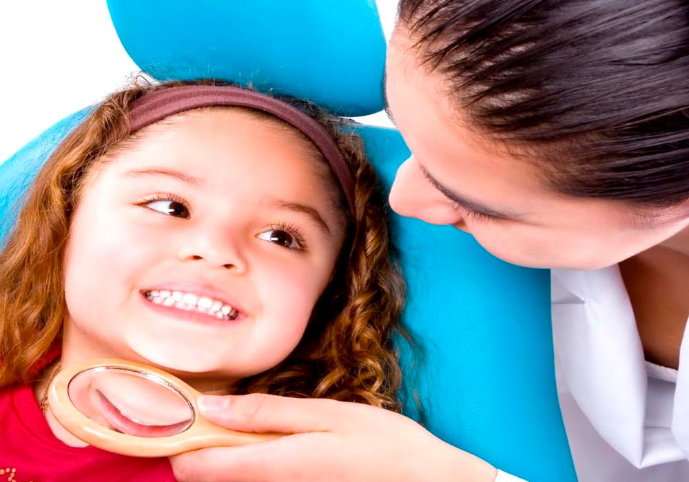 dentist looking at Childs teeth with hand mirror